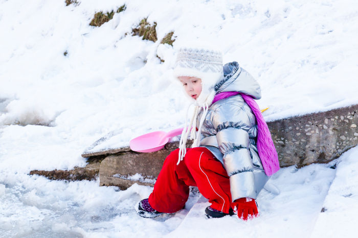 Little girl in snow with pink shovel
