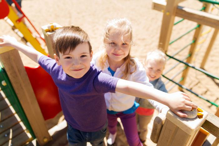 Three kids on a wooden playground