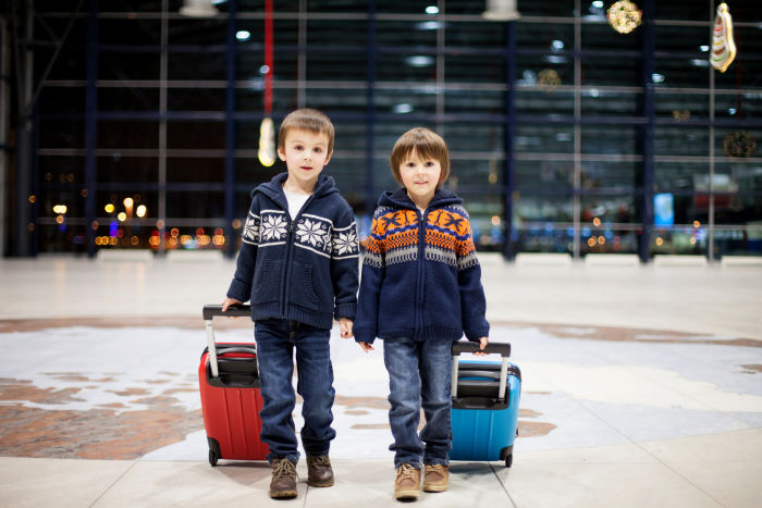 Two little boys pulling suitcases in an airport