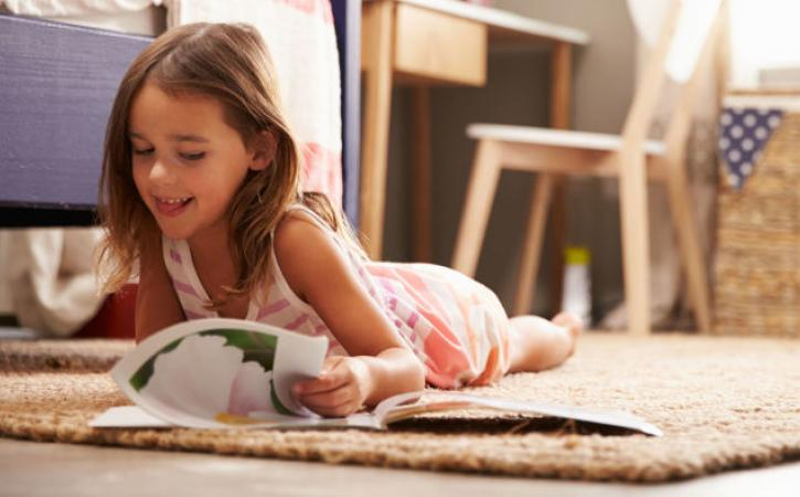Little girl reading book on floor