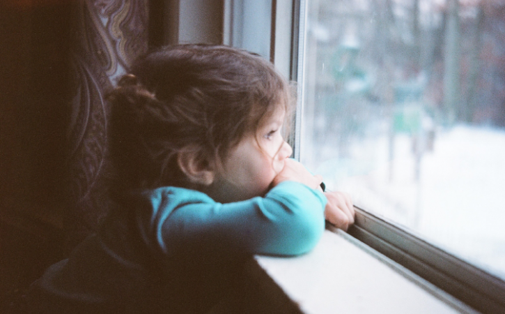 Little girl staring out of window