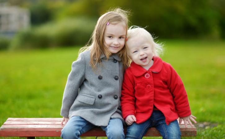 Two little sisters sitting on a park bench