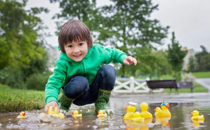 Little boy playing in puddle with rubber ducks