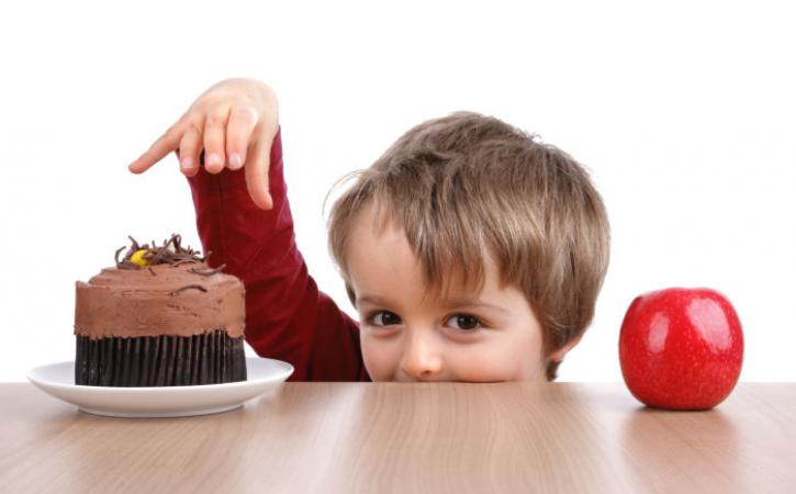 Little boy deciding between apple and cupcake