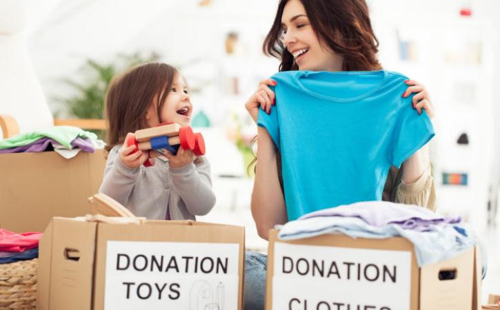 Little girl and mother placing toys and clothes in donation boxes