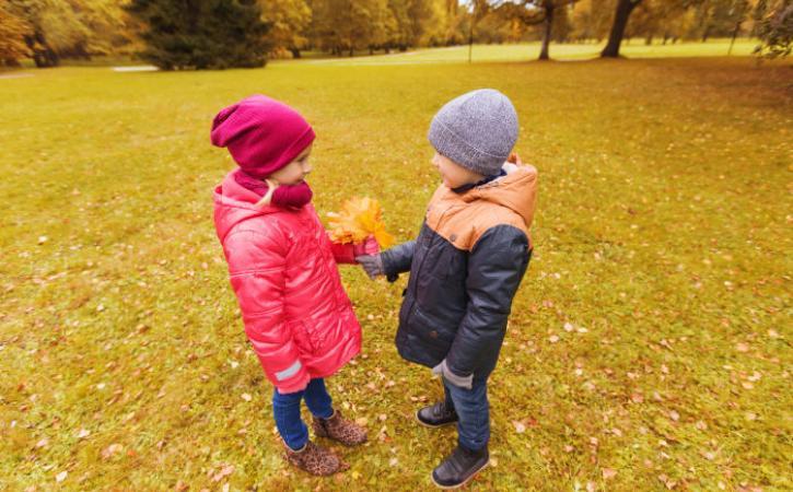 Little boy handing little girl bouquet of leaves