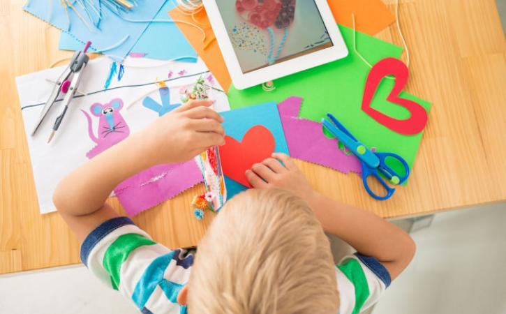 Little boy making a greeting card
