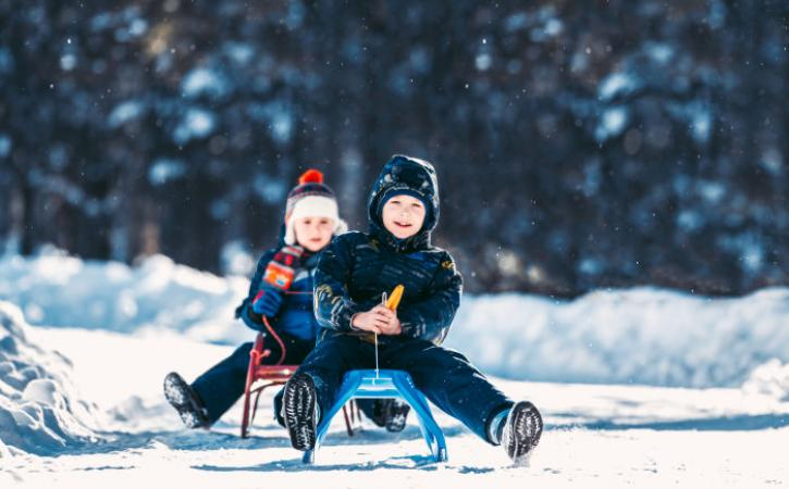 2 boys sledding in snow