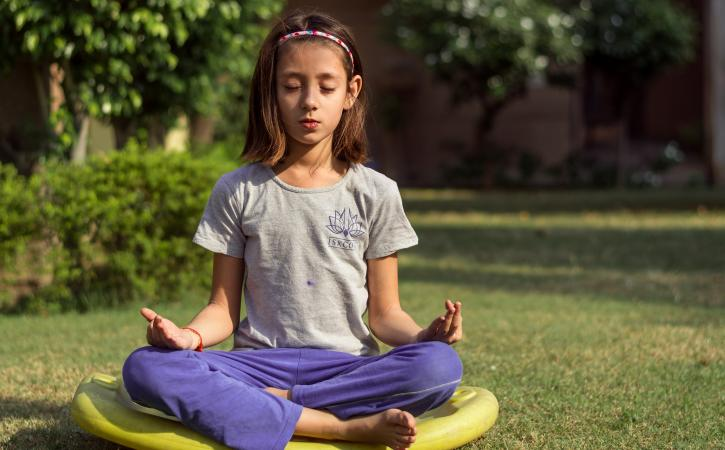 Teaching kids mindfulness - young girl meditating